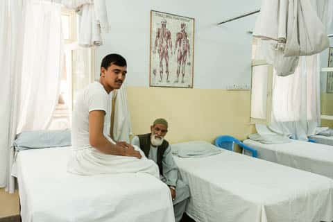 A patient waiting with his father on a hospital bed