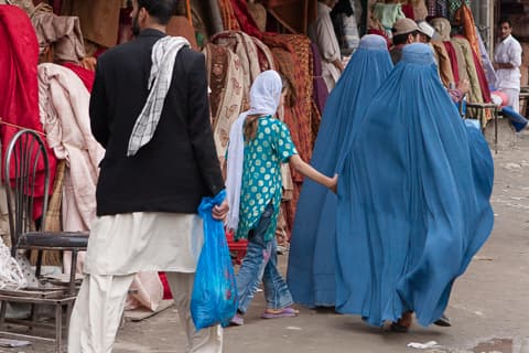 A girl is following two burqa-clad women down the shopping streets of Kabul