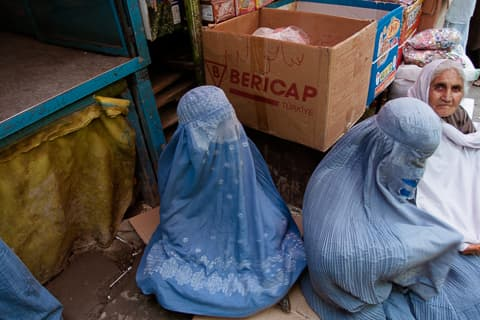 Three veiled women sit on cardboard on the ground in Kabul