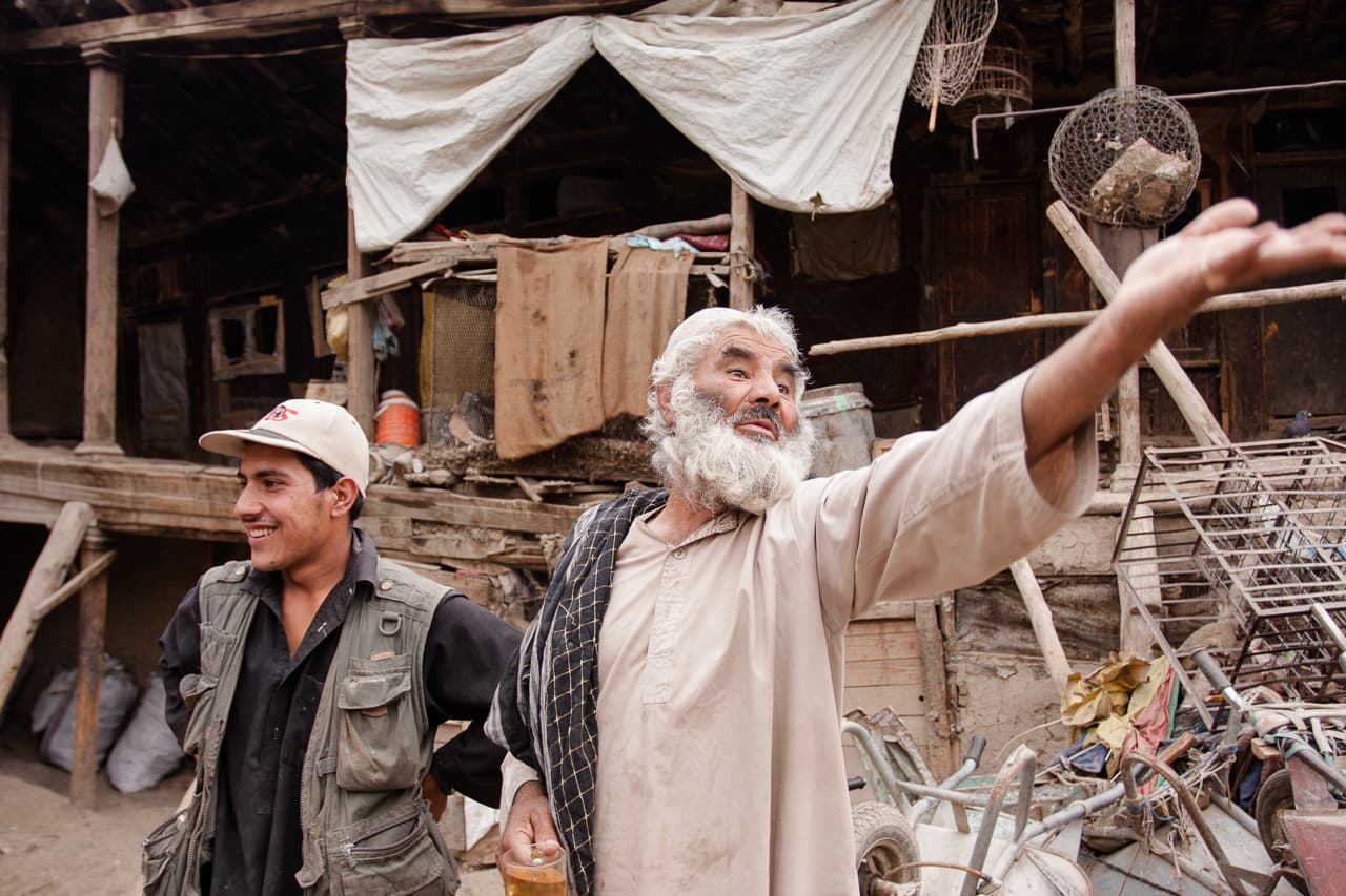 An older man gesticulating around his property in old town Kabul