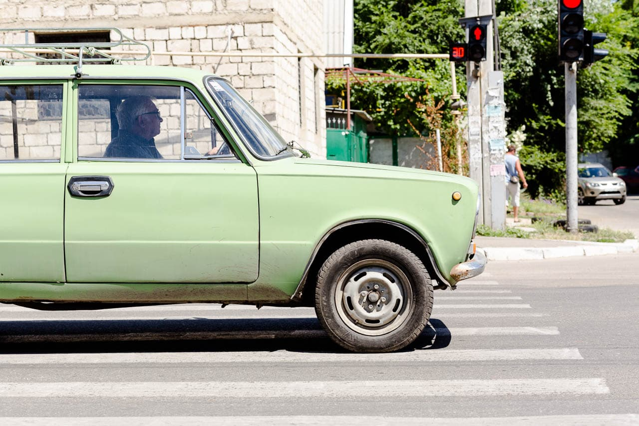 A green Lada at a stop sign