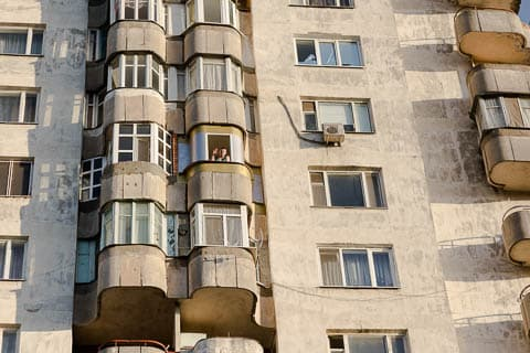 A man waving from a concrete apartment building