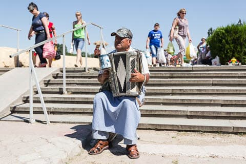 An old male street musician playing the accordion near Alexander Suvorov's statue