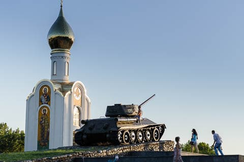A T-34 tank on display in front of an orthodox church