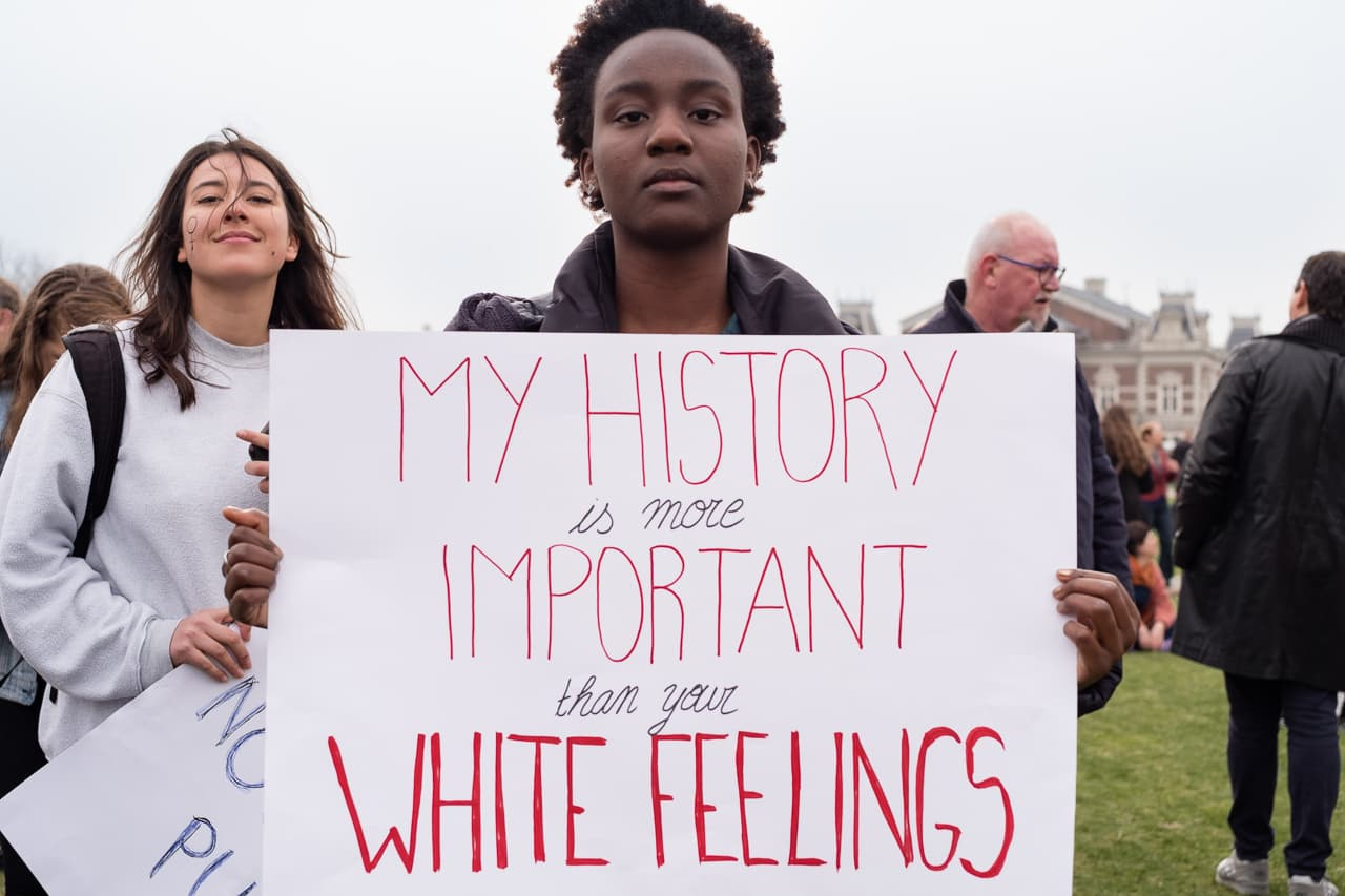 A black woman holding a sign saying 'my history is more important than your white feelings'