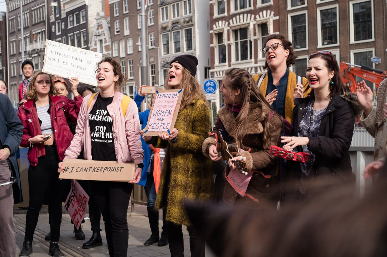 Group of women holding signs and singing with an ukulele on Amsterdam's Rokin street