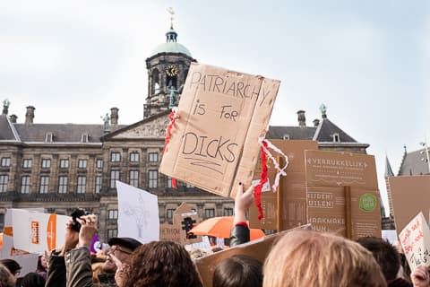 Amsterdam's Dam palace with a sign saying 'Patriarchy is for dicks' in the foreground