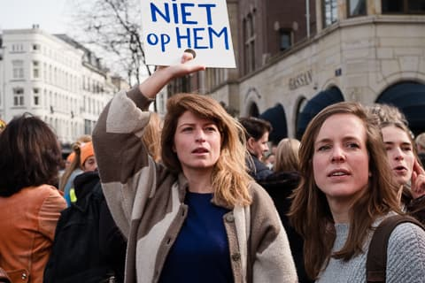 Two women holding a sign on Dam square, looking in the distance