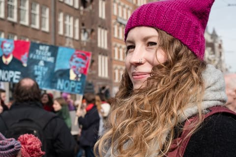 Portraits of a young woman with facial piercings and a purple hat with Donald Trump protest signs in the back