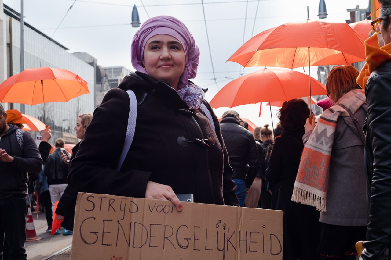 Portrait of a Muslim woman holding a sign with orange umbrellas in the background