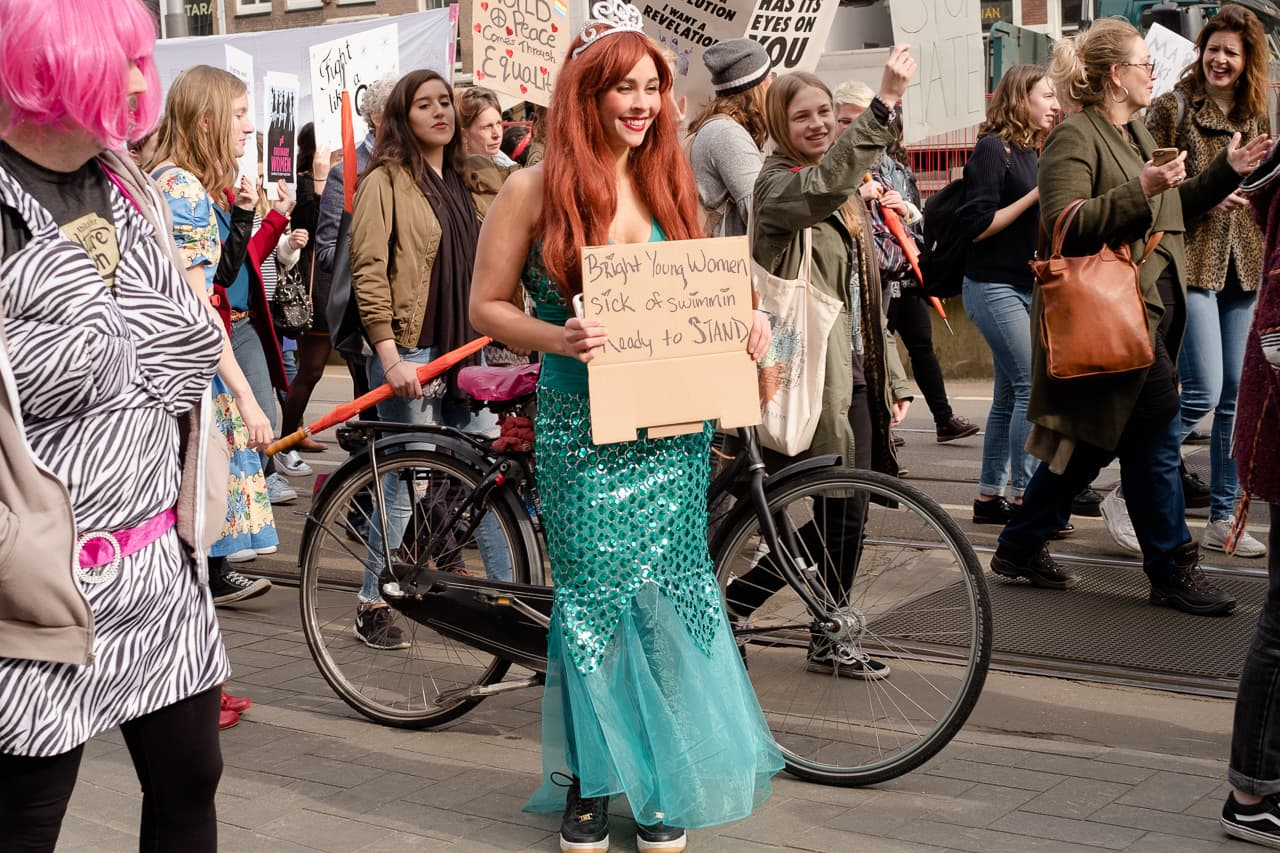 Womanin a mermaid costume with red hair standing amidst the protest