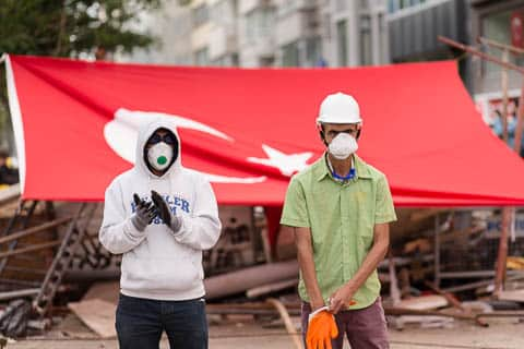 Two youg men with dustmaks in front of a Turkish flag