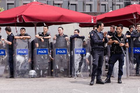 Turkish riot police standing ready with protective gear and shields
