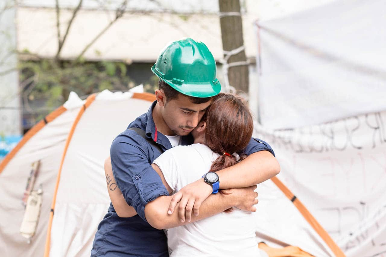A boy wearing a construction helmet hugging a girl with her bloodtype on her arm