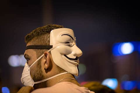 A male protestor wearing a dustmask and a Guy Fawkes mask