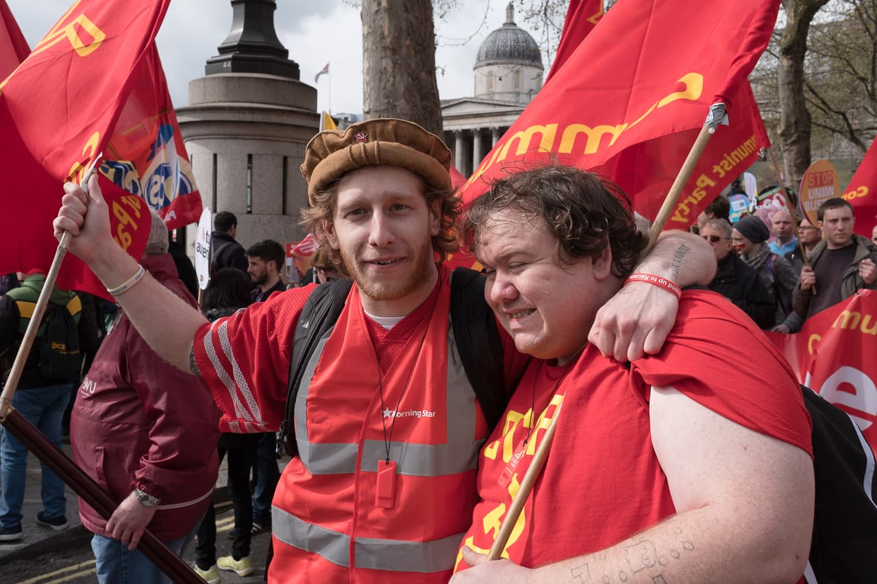 Two men wearing red shirts waving communist flags