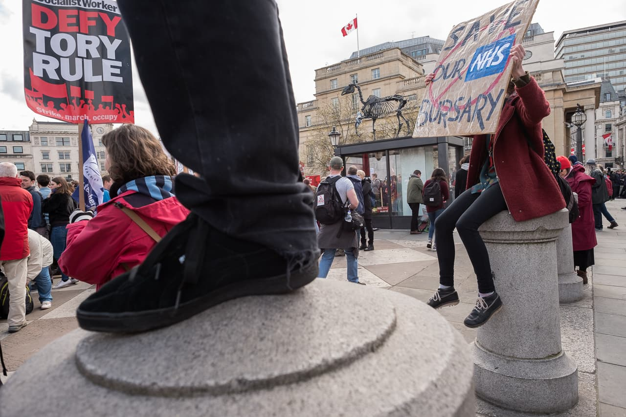 Wideangle shot of people sitting and standing on bollards, holding signs