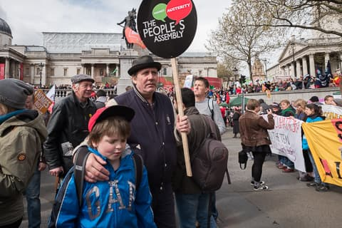 A man holding a sign against austerity and his arm around his son