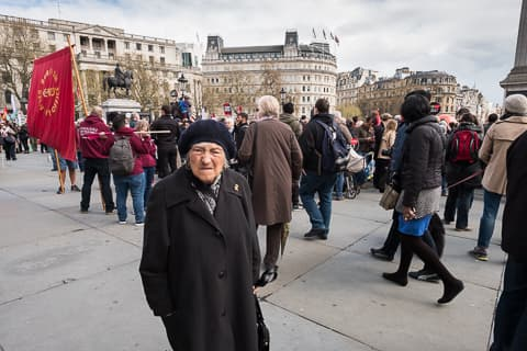 Elderly lady being passed by people attending the demonstration